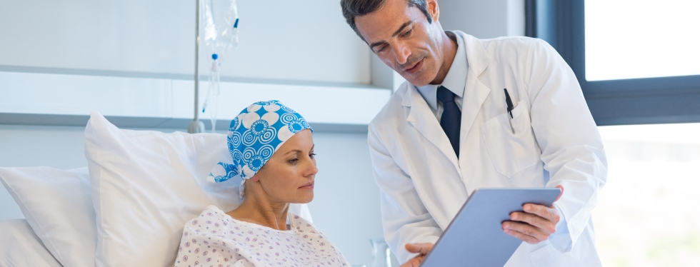 Cancer patent in bed with doctor by her side explaining something in her notes
